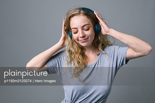 Carefree young woman listening to music with headphones - p1192m2123274 by Hero Images