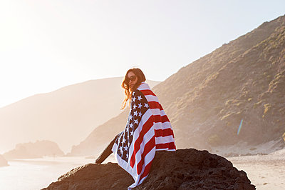 Portrait of woman wrapped in American flag sitting on rock at beach - p1166m1210772 by Cavan Images