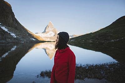 Woman standing by Matterhorn mountain and lake in Valais, Switzerland - p1427m2186490 by Oleksii Karamanov