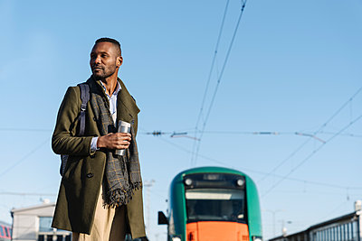 Portrait of stylish man with reusable cup waiting for the train - p300m2154655 by Hernandez and Sorokina