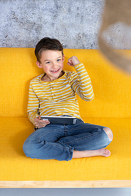 7 year old boy playing with tablet on yellow couch in front of concrete wall - p300m2170382 von Epiximages