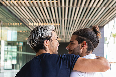 Smiling man with arm around looking at gay partner in city - p300m2226464 by NOVELLIMAGE