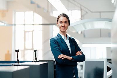 Confident female professional standing with arms crossed in industry - p300m2300269 by Kniel Synnatzschke