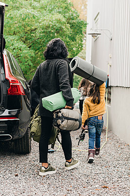 Family unloading luggage from electric car - p426m2195234 by Maskot