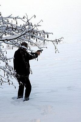 Man behind a tree with a gun - p4760330 by Ilona Wellmann