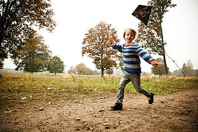 Junge lässt seinen Drachen fliegen - p904m741713 von Stefanie Päffgen
