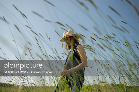 Young woman in hat enjoying nature and sunlight while walking in field - p1166m2112817 by Cavan Images