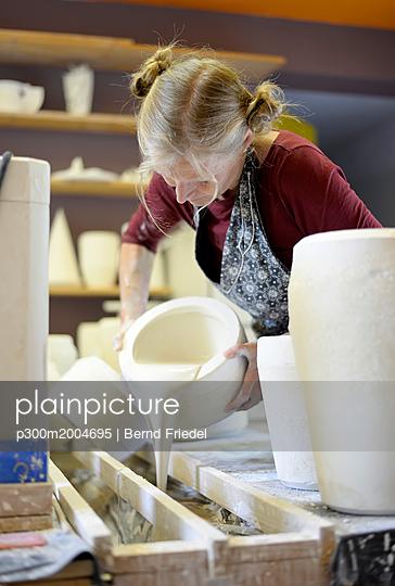 Woman pouring liquid into mold in porcelain workshop - p300m2004695 von Bernd Friedel