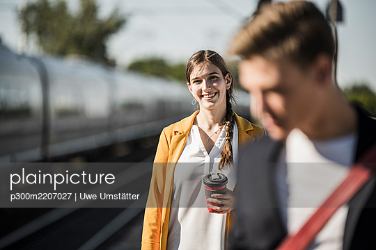 Smiling young woman with reusable coffee mug at railroad station - p300m2207027 by Uwe Umstätter