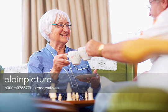 Senior couple playing chess and drinking coffee - p300m978877f by zerocreatives