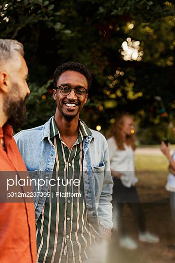 Smiling man in park looking at camera - p312m2237305 by Plattform