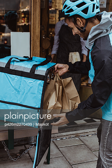 Delivering man putting package order in backpack outside delicatessen shop - p426m2270499 by Maskot