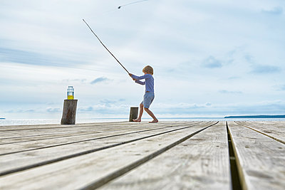 Boy fishing off lakeside dock - p1023m1172720 by Francis Pictures