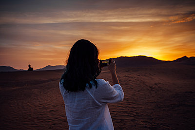 Rear view of woman photographing through mobile phone at desert against cloudy sky during sunset - p1166m1473780 by Cavan Images