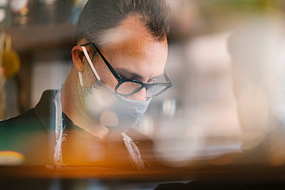 Male barista wearing protective face mask while working in coffee shop during COVID-19 - p300m2220702 by Ezequiel Giménez