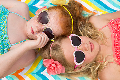 Caucasian girls sunbathing in heart-shaped sunglasses - p555m1408887 by Shestock