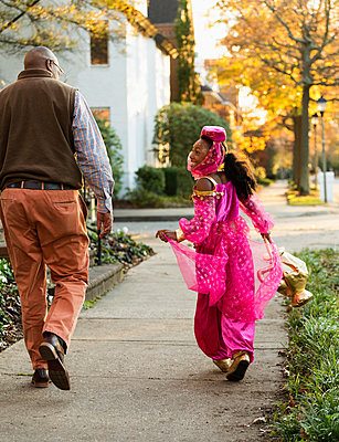 African American girl trick-or-treating with father on Halloween - p555m1413657 by Roberto Westbrook