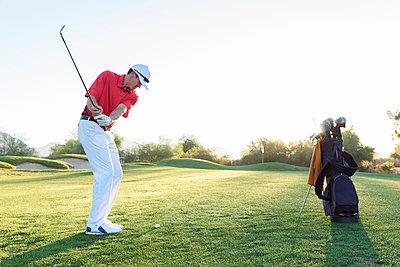 Hispanic man hitting ball on golf course - p555m1472892 by Kolostock