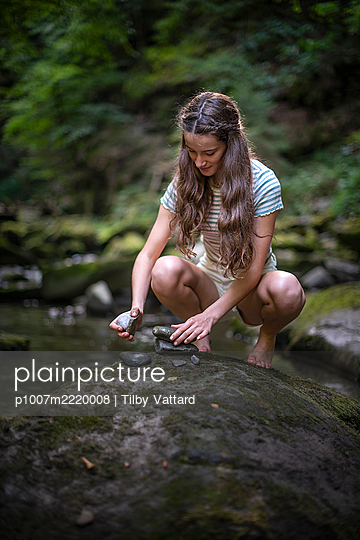 Teenage girl stacking stones in the forest - p1007m2220008 by Tilby Vattard