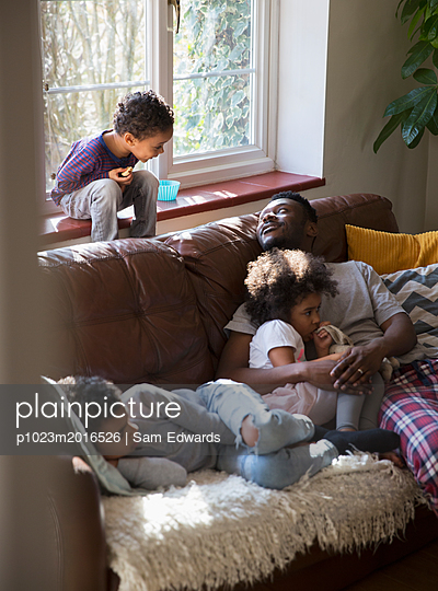 Father and children relaxing, cuddling on living room sofa - p1023m2016526 by Sam Edwards