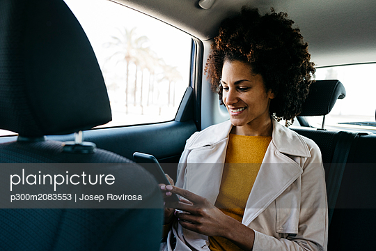 Smiling woman sitting in back seat of a car using cell phone - p300m2083553 by Josep Rovirosa