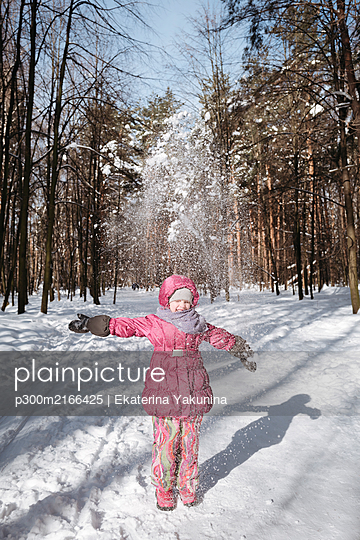 Little girl throwing snow in winter forest - p300m2166425 von Ekaterina Yakunina