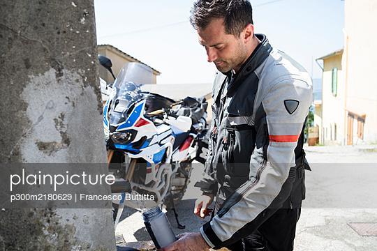 Motorcyclist on a trip having a break at a well - p300m2180629 by Francesco Buttitta
