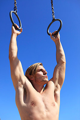 Man with gymnastic rings - p0452803 by Jasmin Sander