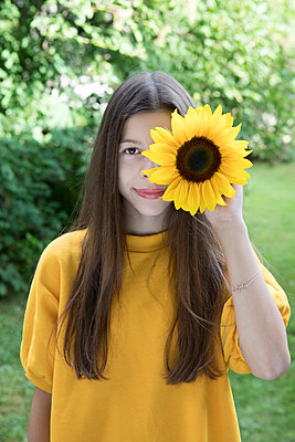 Portrait of smiling girl with sunflower in the garden - p300m2062529 by Petra Stockhausen