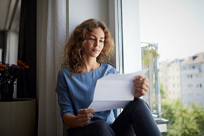 Woman reading paper while sitting on window sill at home - p300m2221408 by Rainer Berg
