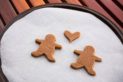 High angle view of gingerbread couple and heart shape on baking sheet - p301m1579842 by Tobias Titz