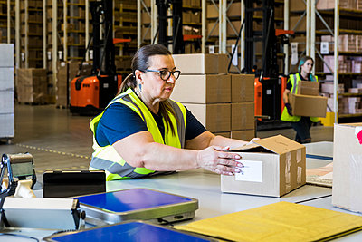 Mature female worker holding cardboard box at desk in distribution warehouse - p426m2018804 by Maskot