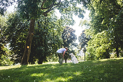 Full length of man talking to dog on grassy field against trees at park - p426m2046365 by Maskot
