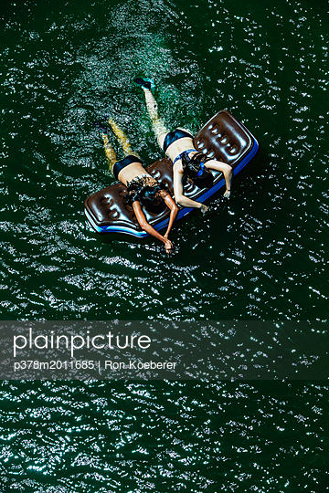 Girls floating on river - p378m2011685 by Ron Koeberer