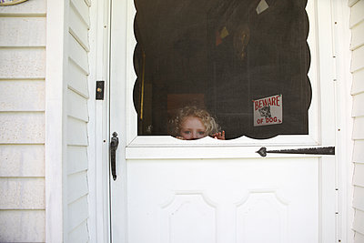 Portrait of girl seen through door - p1166m1489613 by Cavan Images