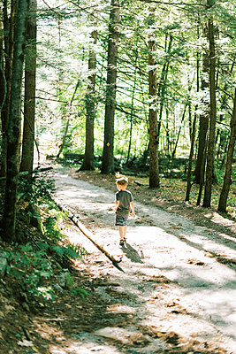 Little boy walking through the woods surrounded by dappled sunshine - p1166m2205697 by Cavan Images