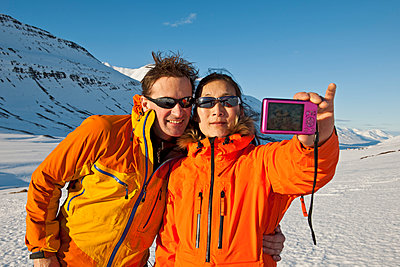 couple taking selfie with compact camera in Iceland - p1166m2269489 by Cavan Images