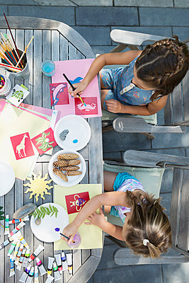 Girls painting at patio table - p1192m1183934 by Hero Images