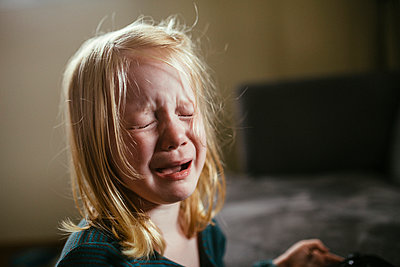 Little Girl With Blond Hair Crying in Window Light - p1238m1042061 by Amanda Voelker