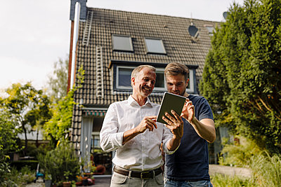 Happy father and son using digital tablet while standing in backyard - p300m2276935 by Gustafsson