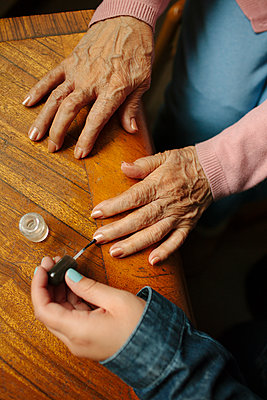 Granddaughter applying painting fingernails of grandmother - p555m1408663 by Shestock