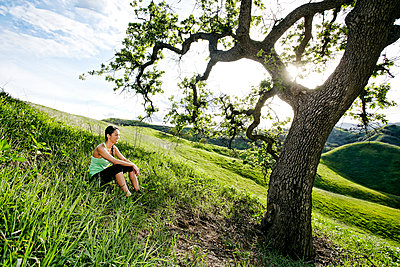 Mixed race athlete sitting on rural hillside - p555m1412194 by Peathegee Inc