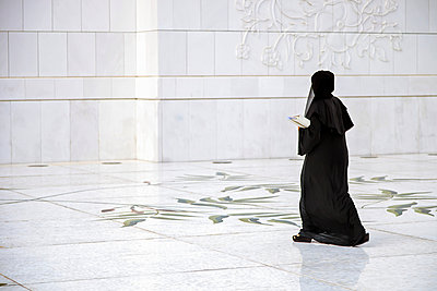 A women in tradidtional dress makes her way to the prayer hall of the  Sheikh Zayed Mosque, Al Maqta district of Abu Dhabi, Abu Dhabi, United Arab Emirates. - p652m972082 by Cahir Davitt