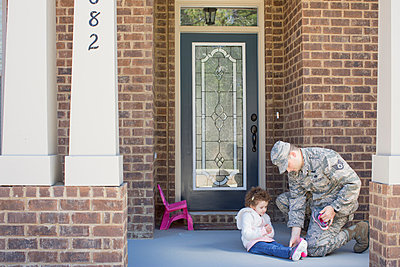 Male soldier putting on daughter's shoes at front door at air force military base - p924m1155162 by Sean Murphy