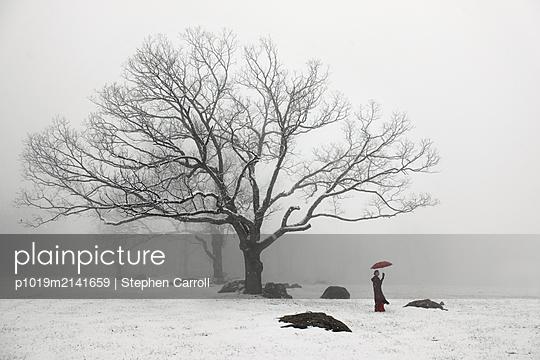 Frau mit Regenschirm im Schnee - p1019m2141659 von Stephen Carroll