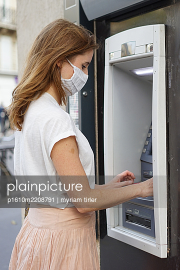 A woman wearing a cloth mask draws money at the cash machine - p1610m2208791 by myriam tirler