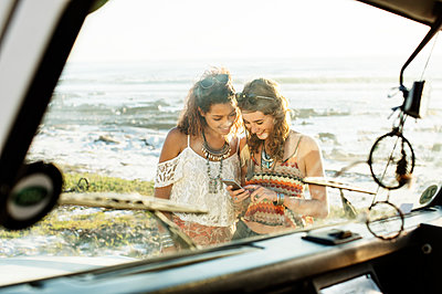 Happy friends using mobile phone at beach seen through windshield - p1166m1226179 by Cavan Images