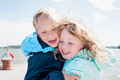 portrait of brother and sister laughing at the beach together - p1166m2201762 by Cavan Images