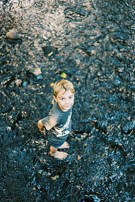 A five year old boy getting his feet wet in a river - p1166m2205702 by Cavan Images