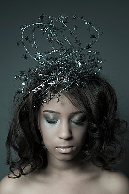 Young black woman with a glittery crown, eyes closed. - p1433m1589016 by Wolf Kettler